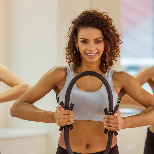 Three attractive sport girls smiling while working out with pilates ring in fitness class